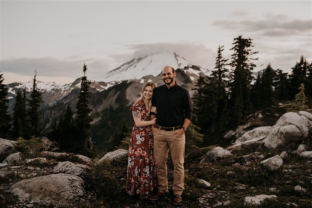 two people smiling in front of a mountain